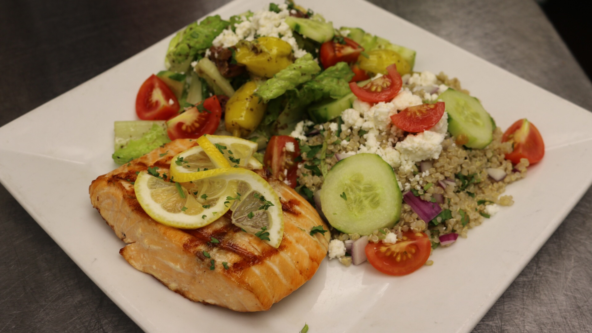 Fresh grilled salmon with a side of lemon basil rice and a small greek salad