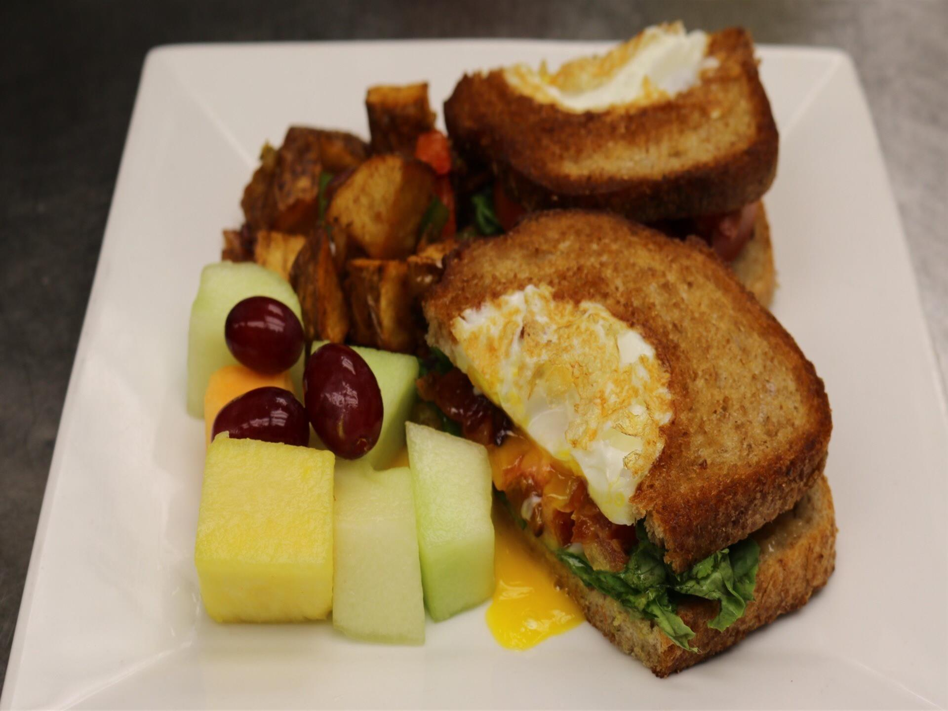 Over easy egg sandwich with a side of fruit and potatoes