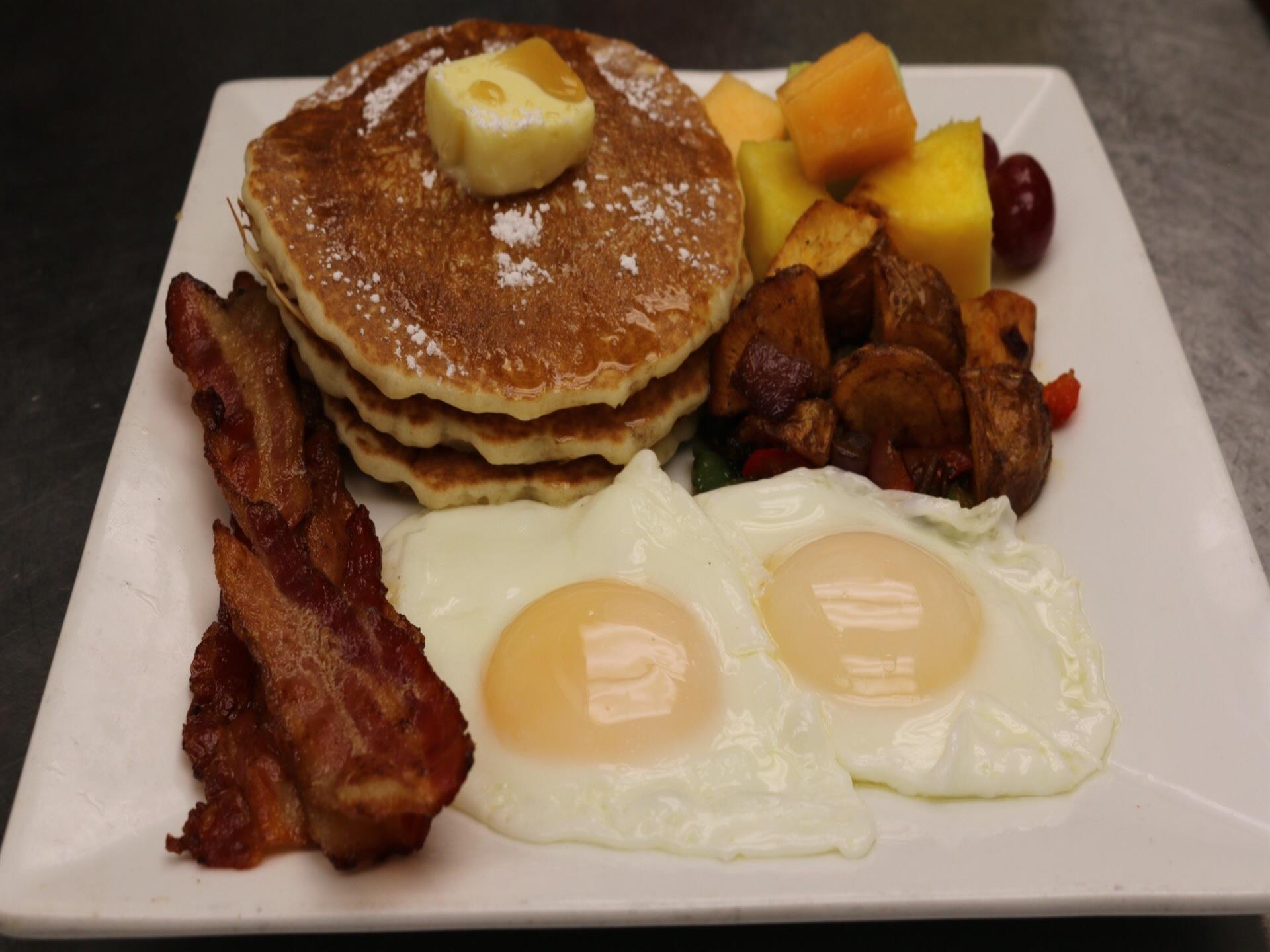 Two sunny side up eggs with 2 strips of bacon, short stack of pancakes, potatoes and fruit
