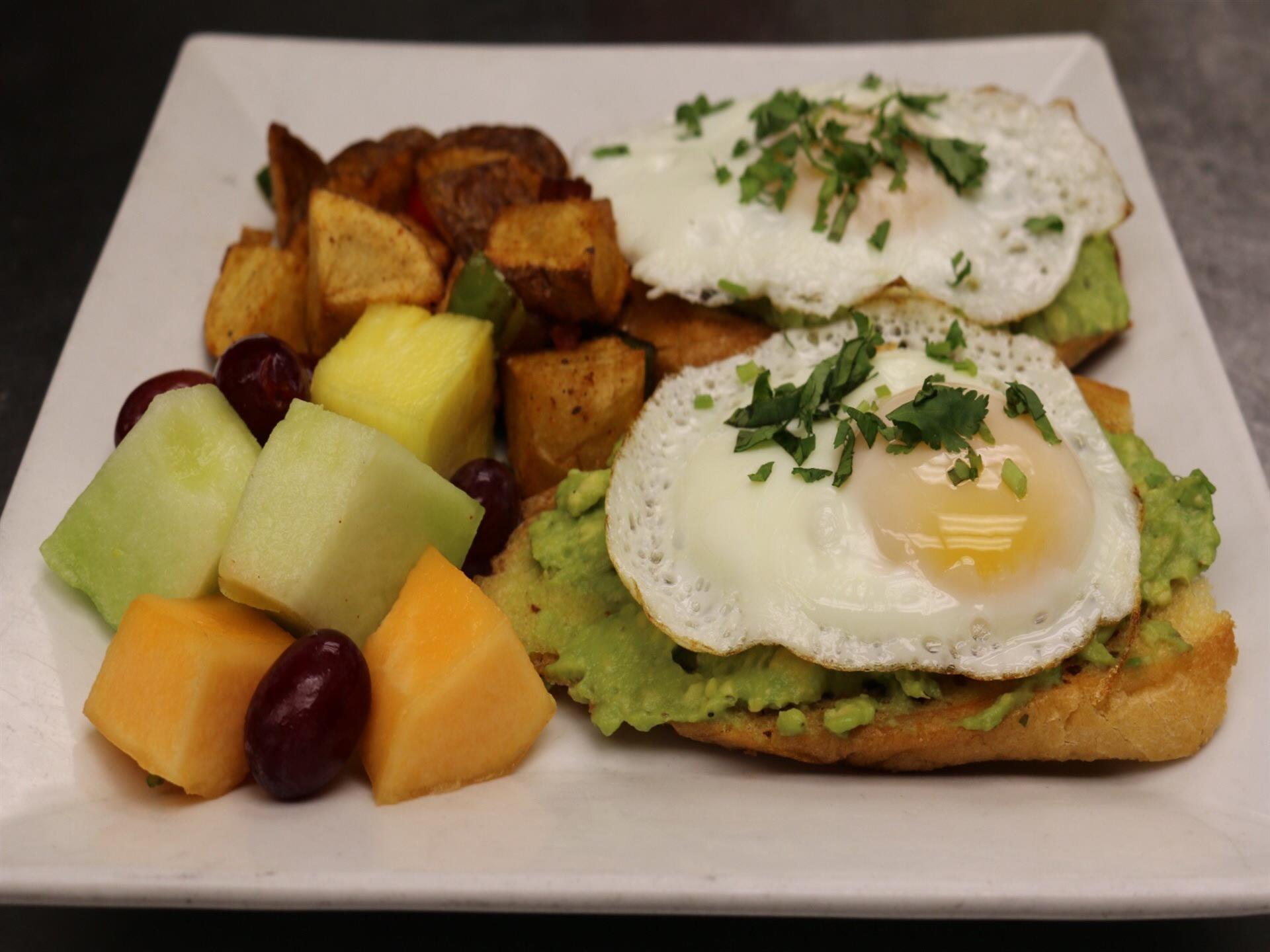 two pieces of avocado toast with sunny side eggs with a side of potatoes and fruit