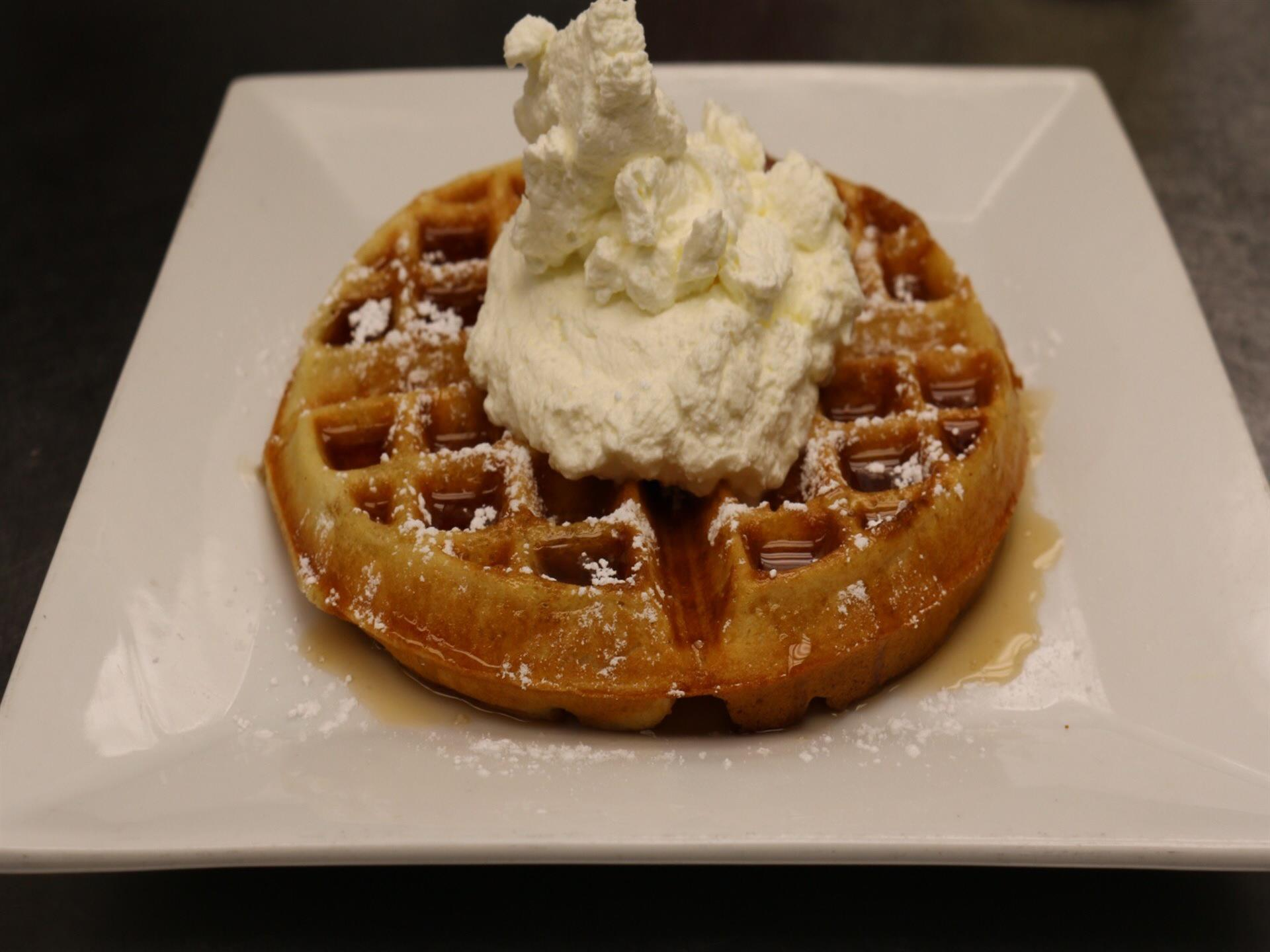 Belgian waffle topped with syrup, ice cream and whipped cream