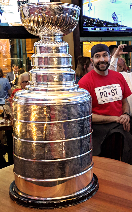 man smiling at the stanley cup
