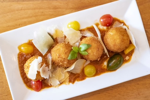 deep fried risotto balls topped with tomatoes