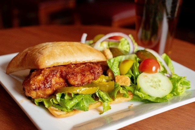 chicken sandwich with pickles and a side salad