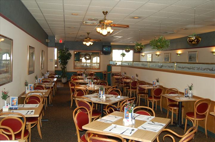 inside of TJ's Of Calverton Restaurant with tables and chairs