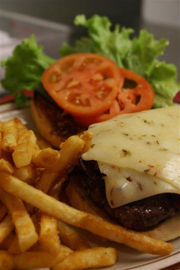 an open burger wuth cheese, tomato and lettuce with fries on the side