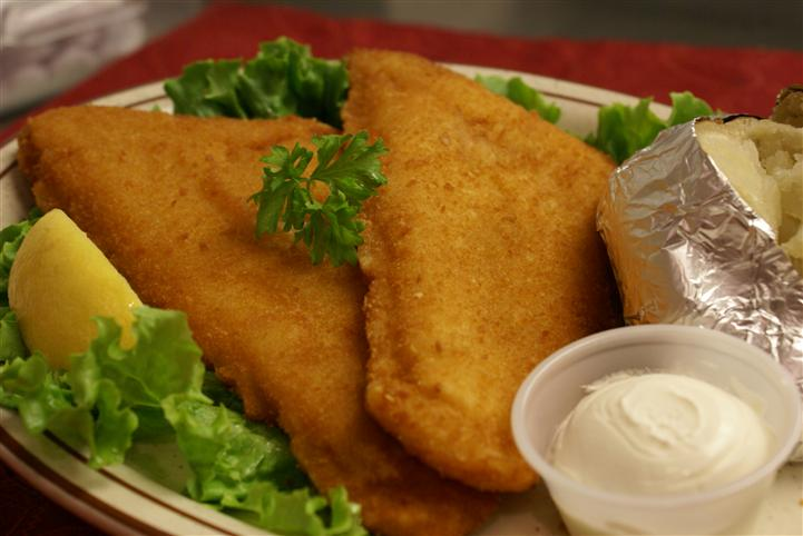 Fried menu item on top of lettuce with sour cream on the side