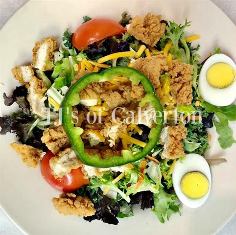Salad with a hard boiled egg, peppers and breaded chicken