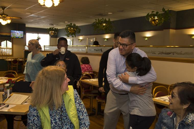 A dad and daughter hugging inside the restaurant