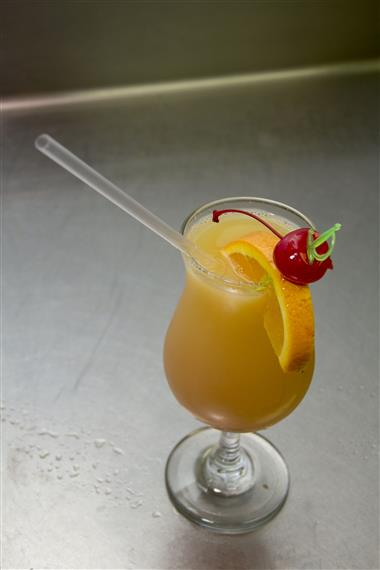cocktail with orange juice. garnished with an orange and a cherry
