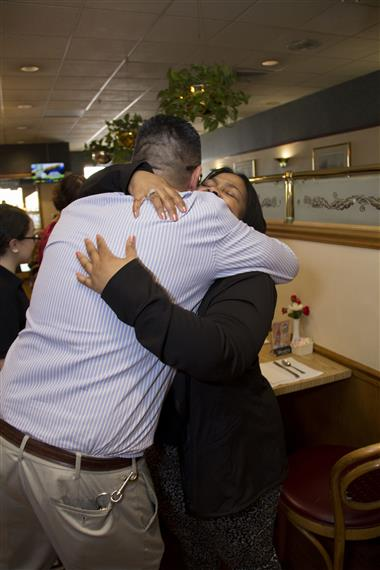 the owner hugging customers inside