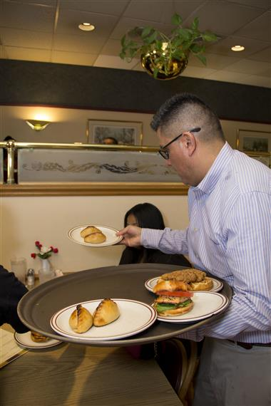 The owner serving food to customers inside