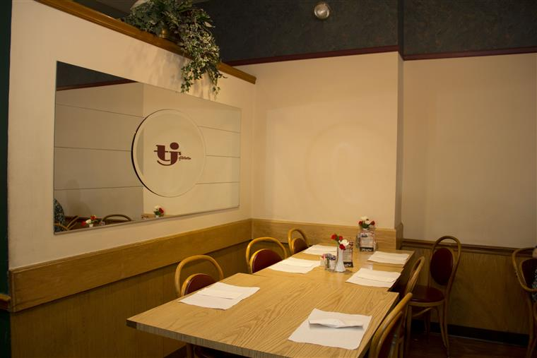 Inside TJ's Of Calverton Restaurant with logo printed on the mirror in the back