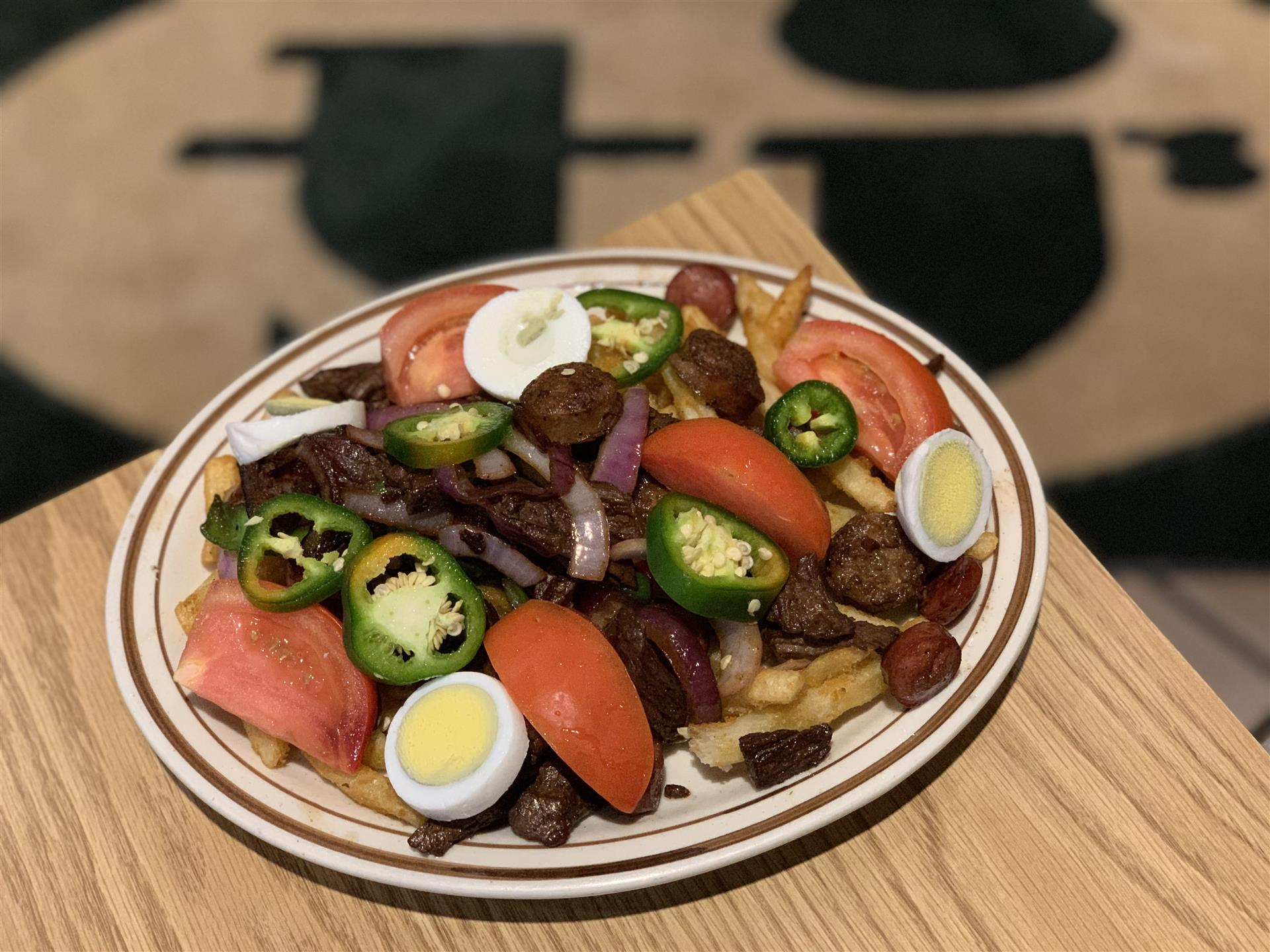 tomatoes, hard-boiled eggs, jalapeños on a plate of fries