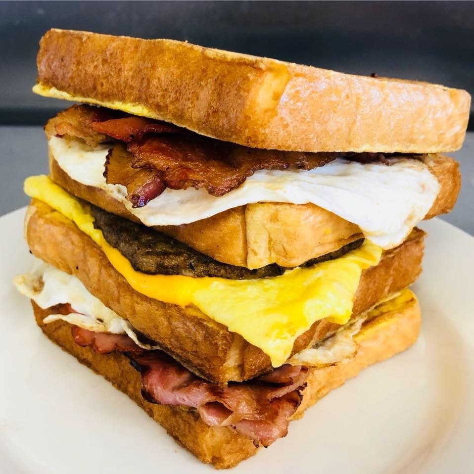 Triple stacker Egg sandwhich on toast with bacon and cheese