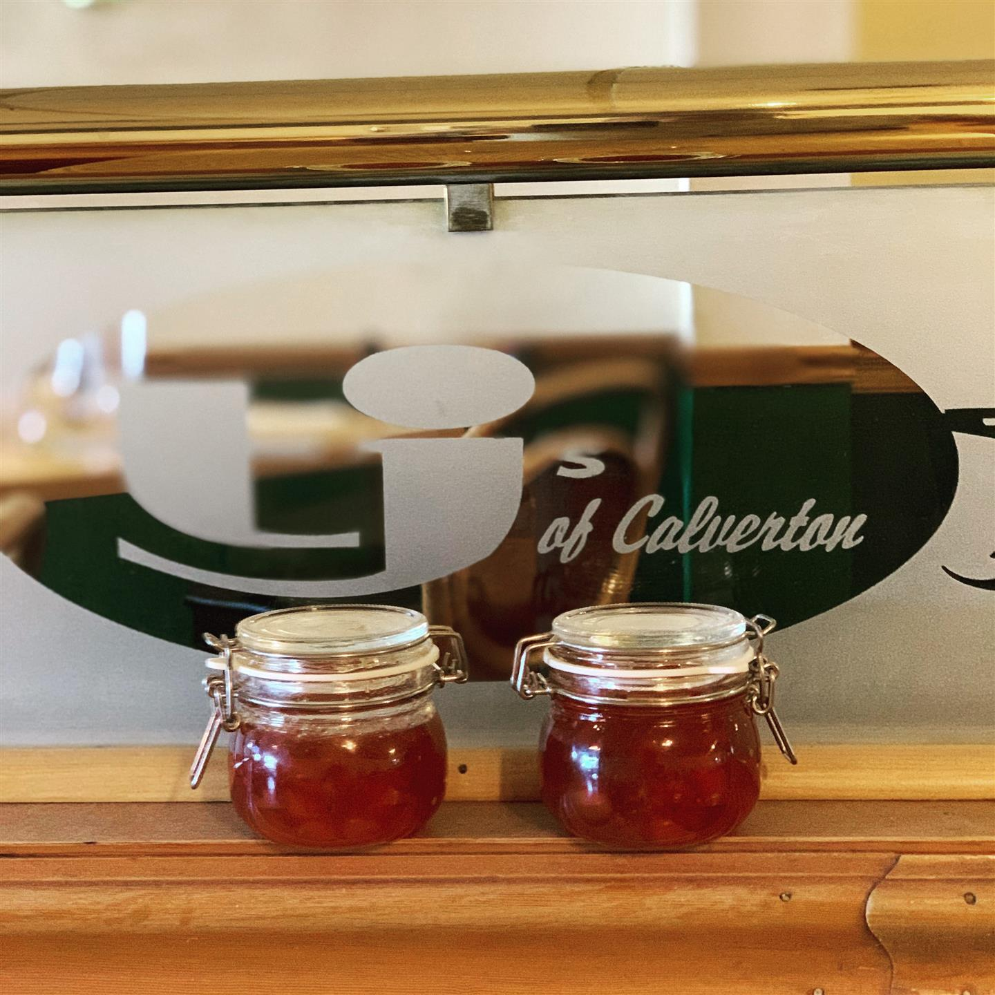 jam in jars sitting on the ledge in front of the logo