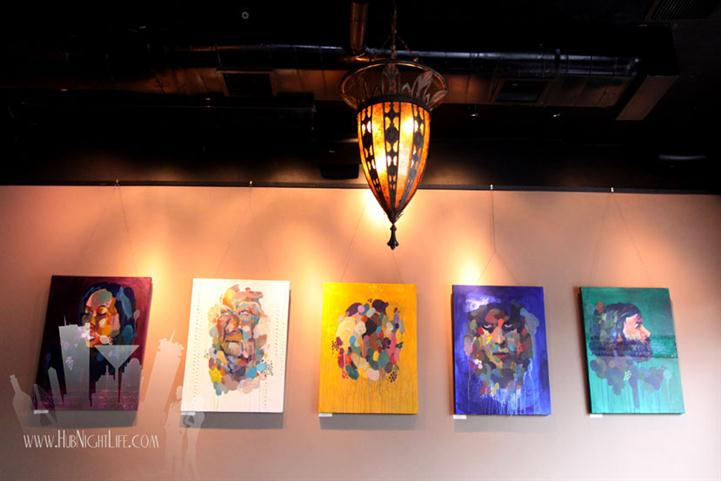 Light fixture hanging from the ceiling with canvases og colorful art in the background hanging from the wall