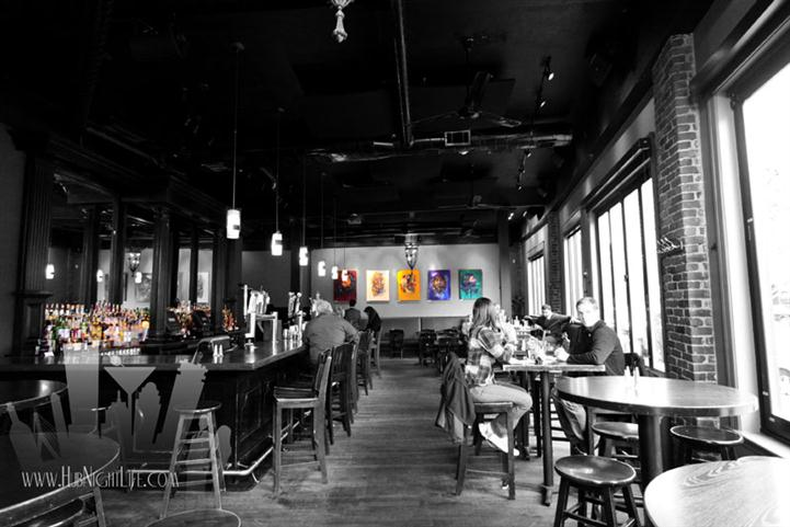 Black and white photo of the bar hall with pops of color from the art on the back wall