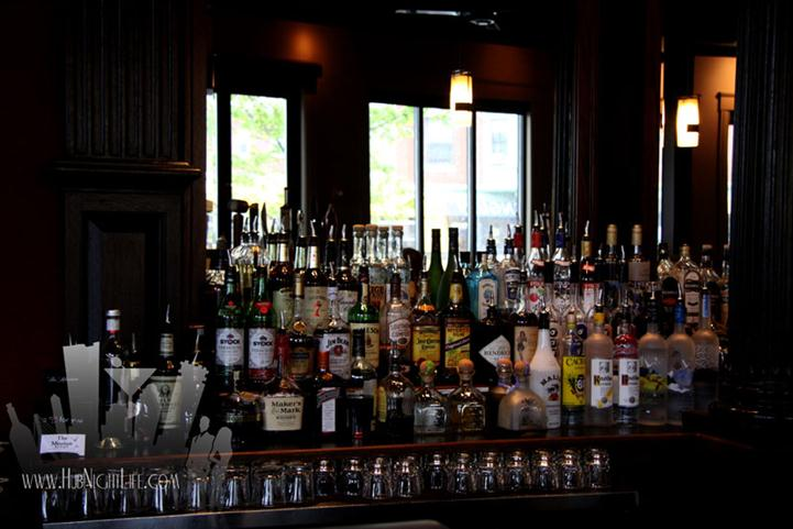 Liquor display with a variety of bottles and glasses in the bar