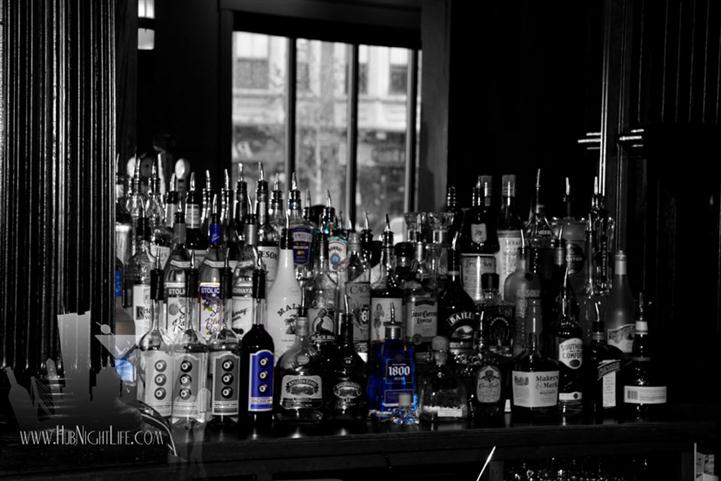Black and white photo of the liquor display of various bottles