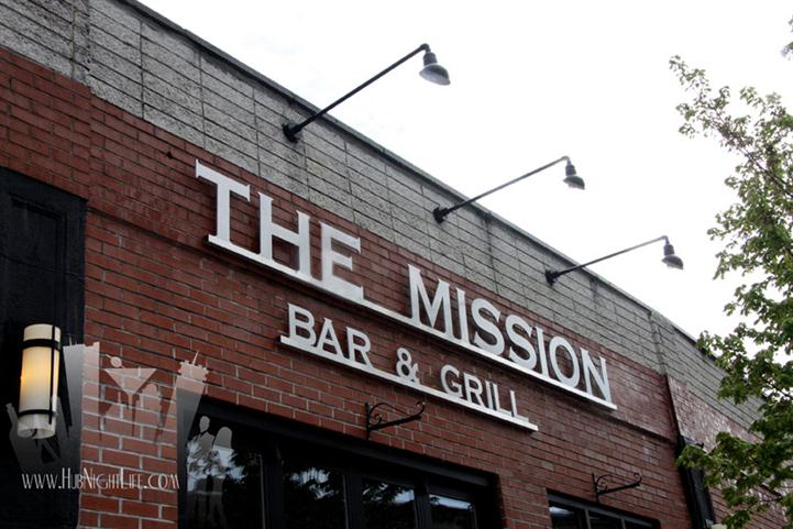 Outdoor photo of the bar sign on the brick wall and the metal lights from above