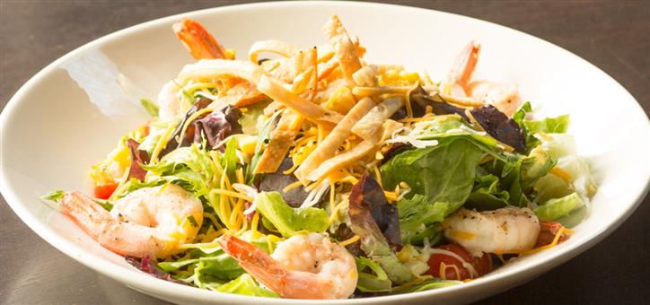 Shrimp salad with mixed greens and shredded cheese served in a white bowl