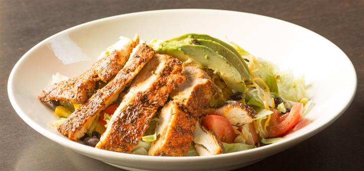 Grilled chicken served over mixed salad greens and avocado slices