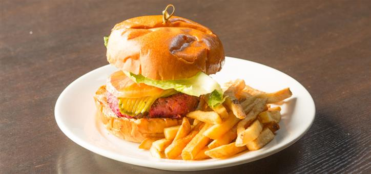 Burger with lettuce, onion, tomato, cheese and pickles served with skinny fries