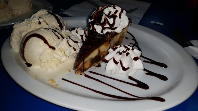 Slice of pie with ice cream, whipped cream, and chocolate drizzle on dish