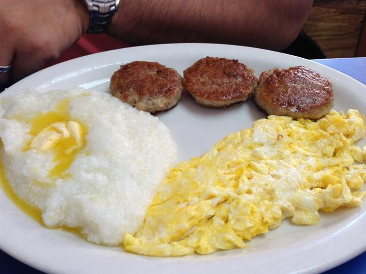 Scrambled eggs, grits with butter, three sausage patties