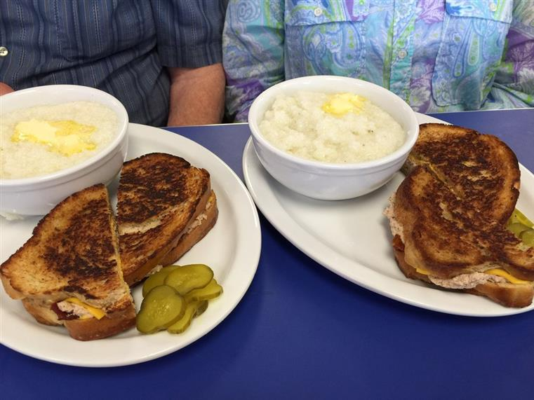 Two customers with identical dishes. Tuna bacon melts, side of pickles, and bowl of grits.