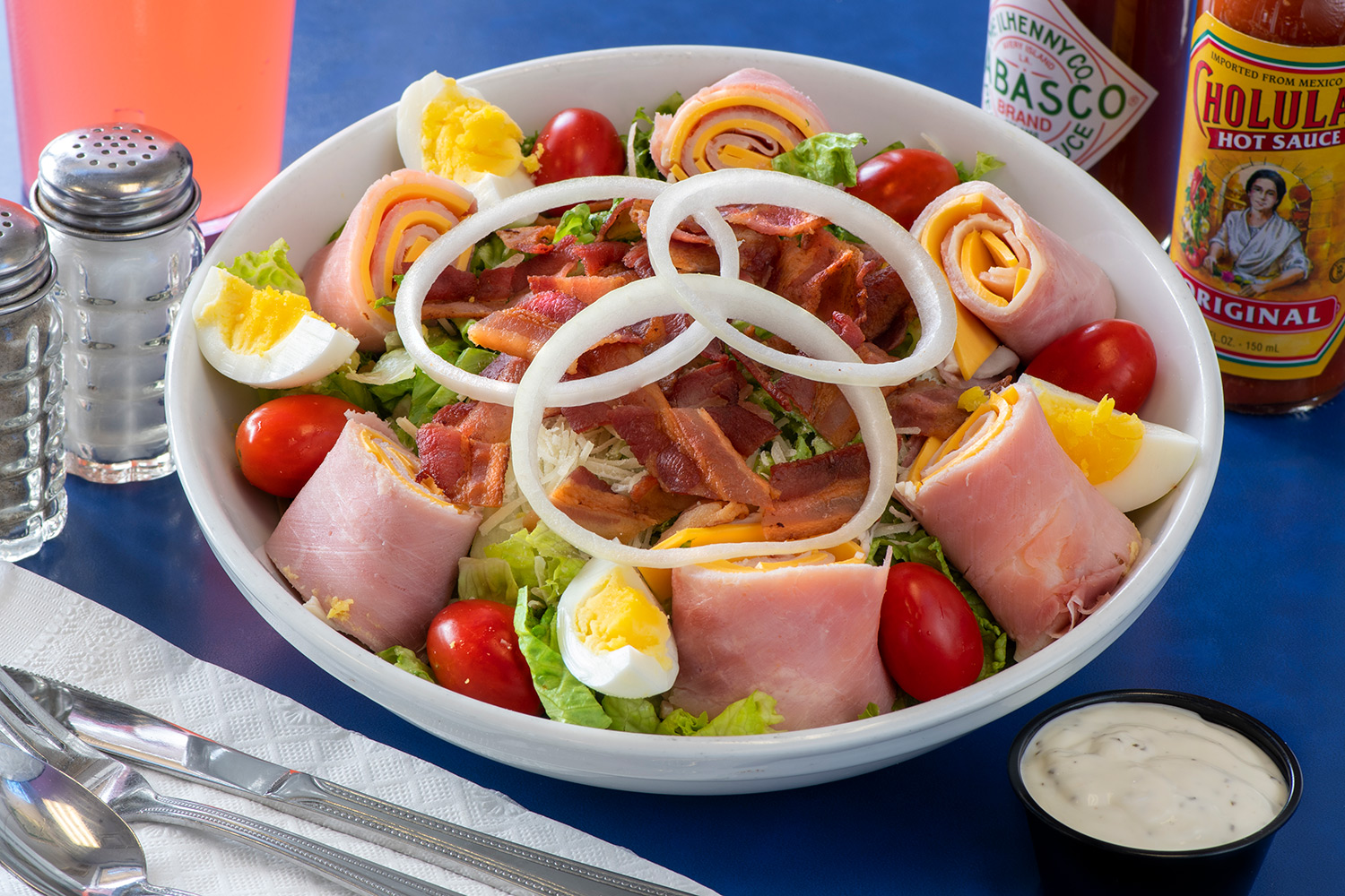 Chef salad with ham, cheese, onions, hard boild eggs and tomatoes
