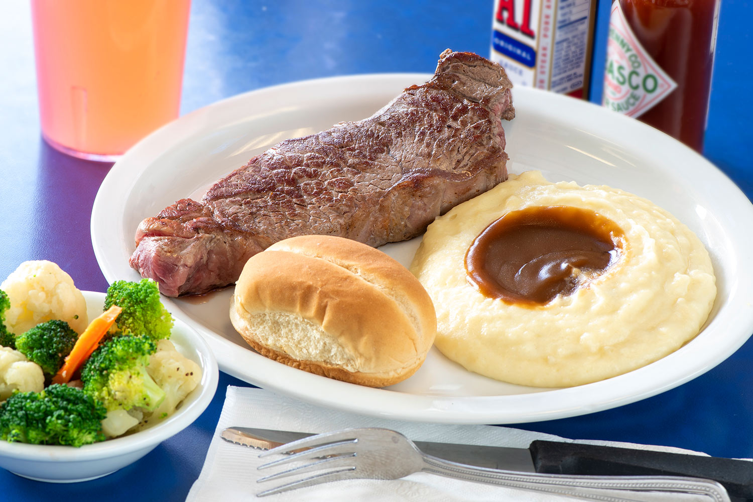 New York Steak with mashed potatoes and a roll