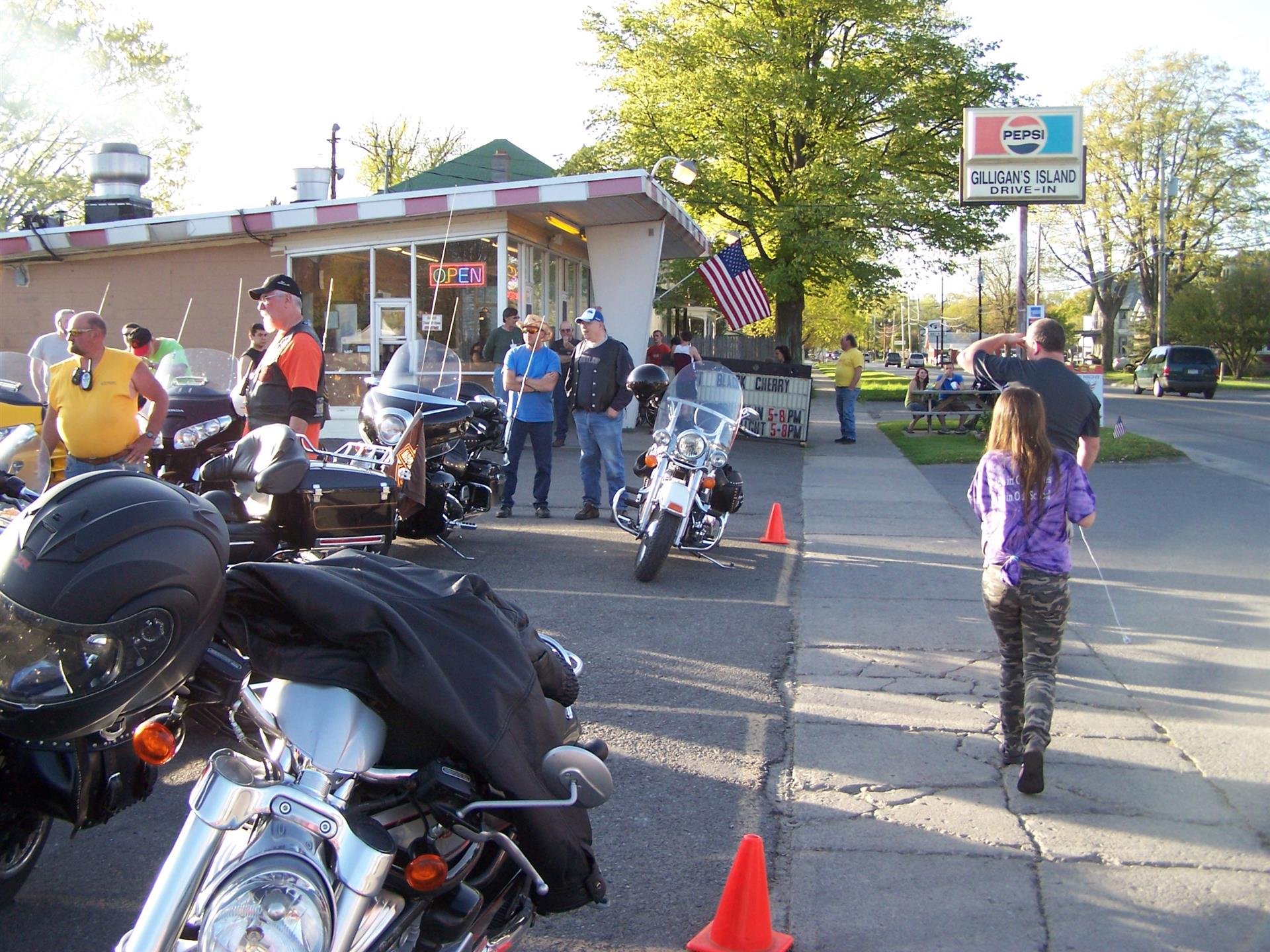 People in parking lot looking at bikes in front of Gilligans Drive In