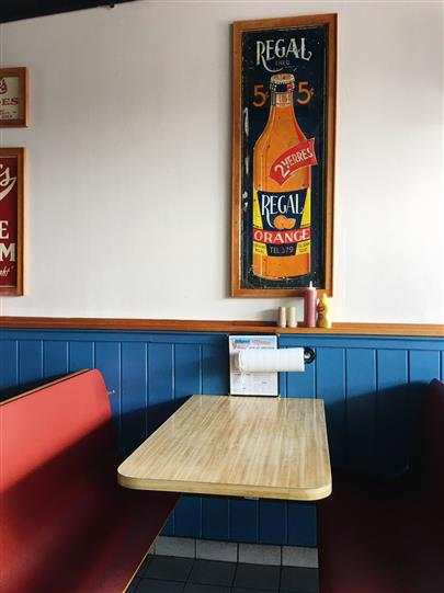 Dining booth with regal orange artwork on wall