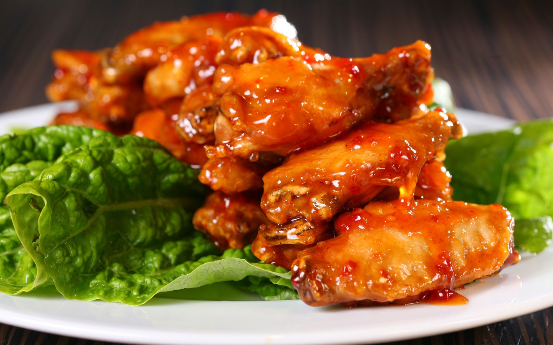 Buffalo chicken wings on a plate over lettuce