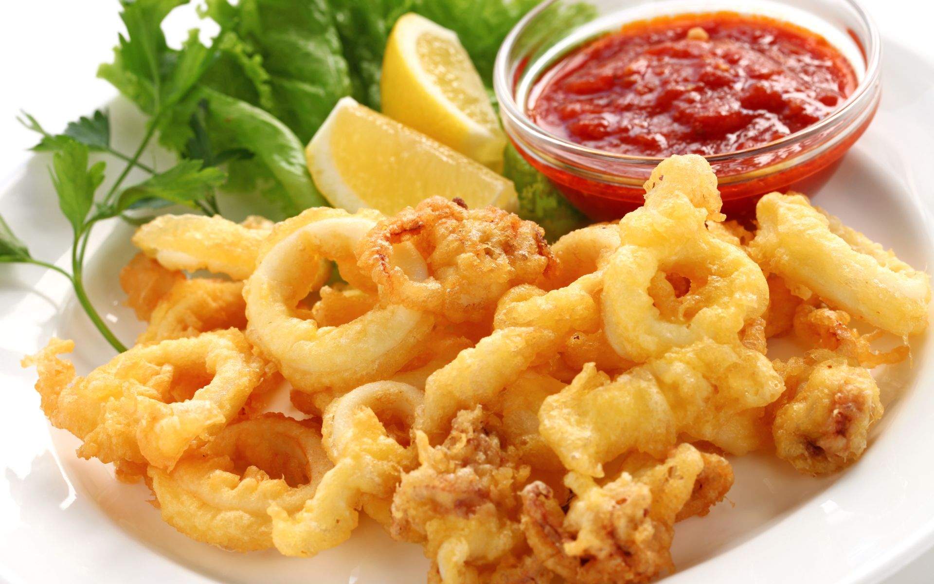Fried calamari on a plate with lemon and marinara sauce