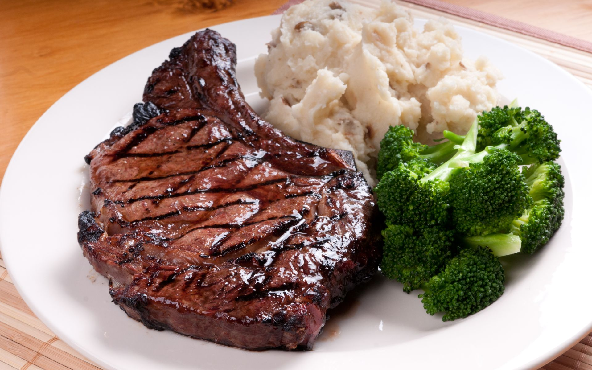 Grilled steak on a plate with mashed potatoes and broccoli