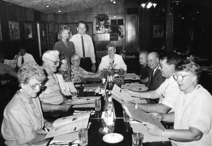 Black and white image of 11 people around a table looking at menus.