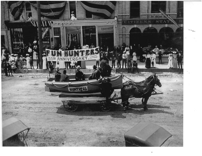 Black and white image of two horses pulling a boat on wheels in a parade.