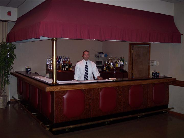 Inside of banquet area, view of the bar and bartender.