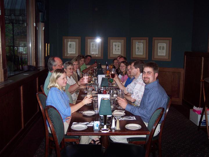 Group of about 13 guests at dining table raising their glasses.