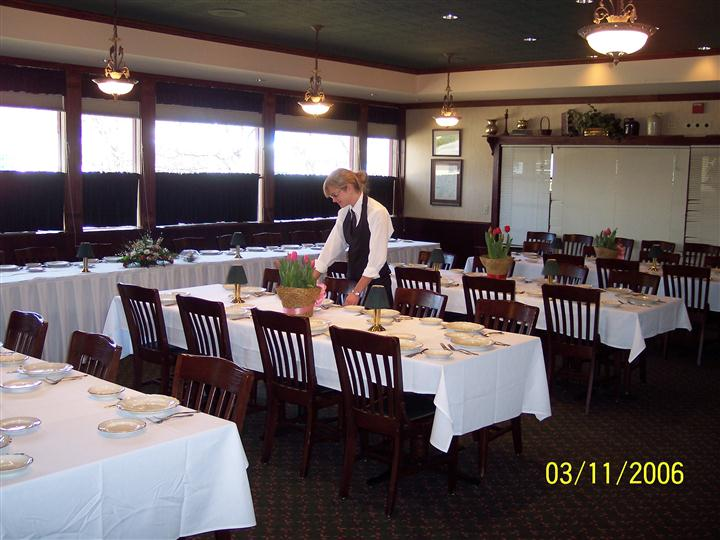 Inside banquet room set for event with potted flowers on the table. Female staff member is setting the table.