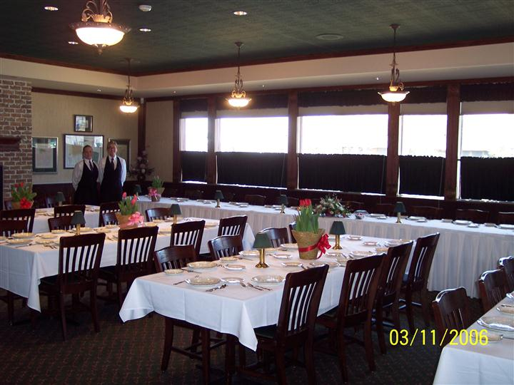 inside banquet room set for event with two staff members in the background.