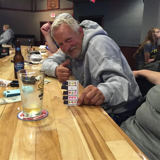 Man leaning over table holding a card that he is showing to the camera.