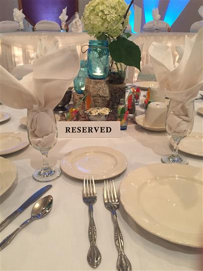 Close up of table setting reserved with white linens and plates and a blue mason jar with a plant as the centerpiece.
