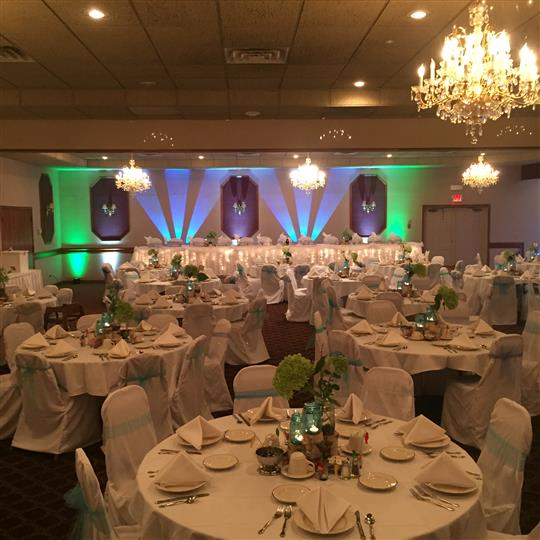 Indoor view of banquet room set for event with white linens and blue bows tied around the chairs.