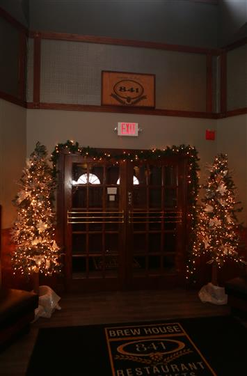 Double doors inside the restaurant that is aligned with garland and lights with one decorated Christmas tree on each side.