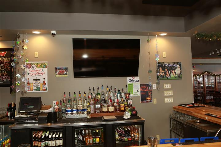 Behind the bar display of liquor and flat screen tv.