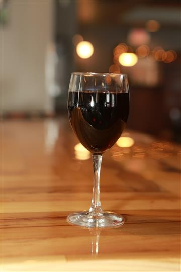 Almost full glass of red wine.